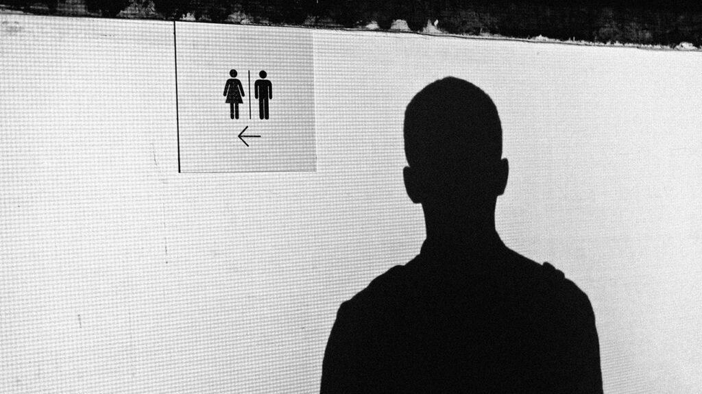 A black and white image of a silhouette looking at a sign portraying the male and female icons.