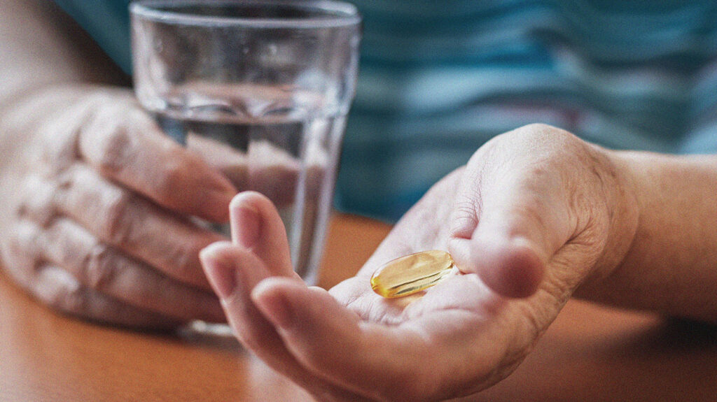 A person holding fish oil capsules in one hand and a glass of water in the other.