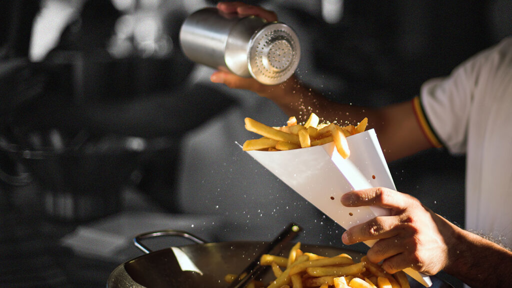 a close up image of a person shaking salt onto a cone of french fries, which are of many foods high in sodium