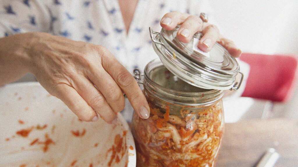 A close up of a person holding an open jar containing kimchi that may contain lactic acid.
