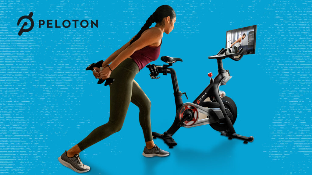 Woman exercising using Peloton bike, isolated over blue background next to Peloton logo