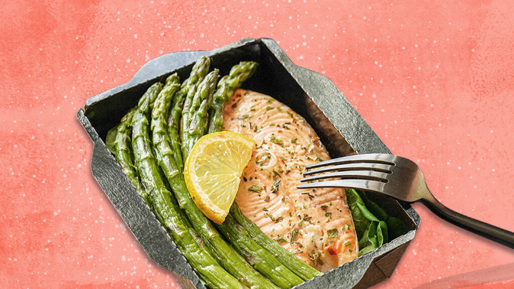 Plate of salmon and asparagus from meal delivery for weight loss over pink background