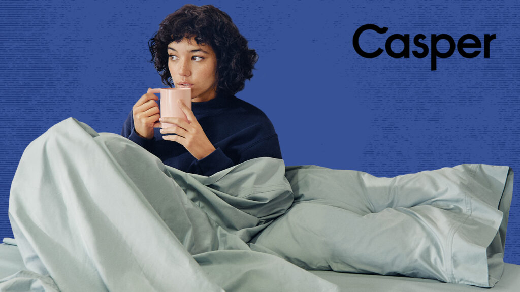 Photo of woman sitting in bed drinking from mug over blue background next to blue background
