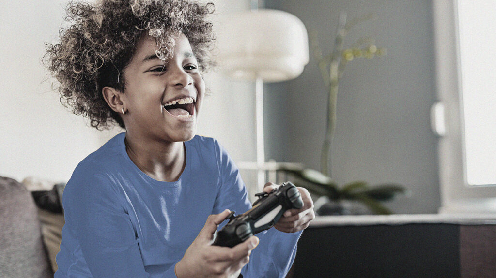 Smiling child plays video games.