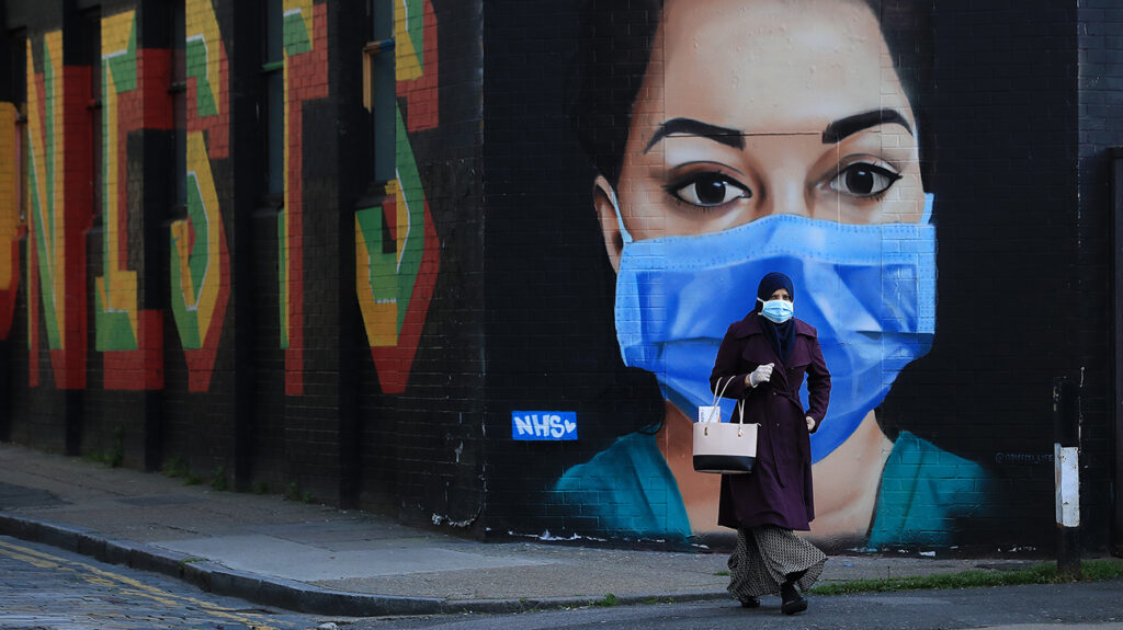 LONDON, ENGLAND - APRIL 21: A woman wearing a face mask walks past a piece of street art depicting an NHS worker on April 21, 2020 in the Shoreditch area of London, England. The British government has extended the lockdown restrictions first introduced on March 23 that are meant to slow the spread of COVID-19. (Photo by Andrew Redington/Getty Images)