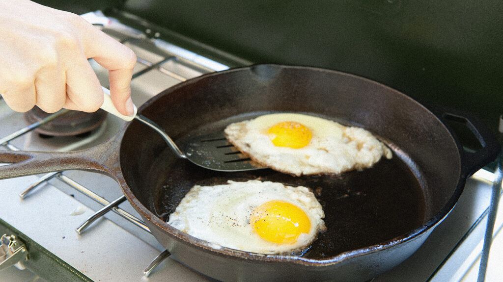Two eggs being fried in a pan.