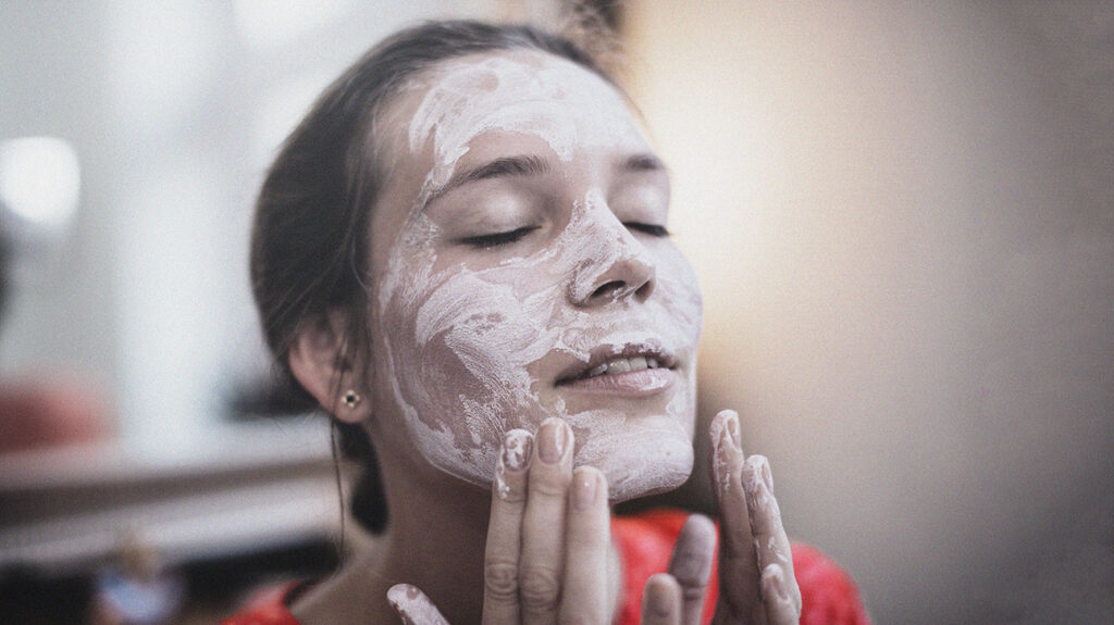 Person using caprylic triglyceride product on face.