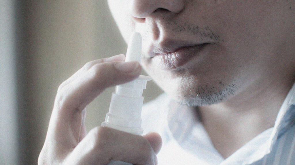 close up of man about to use nose spray