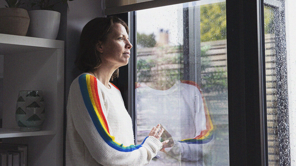 A woman experiencing symptoms of anxiety who is looking out of a window.
