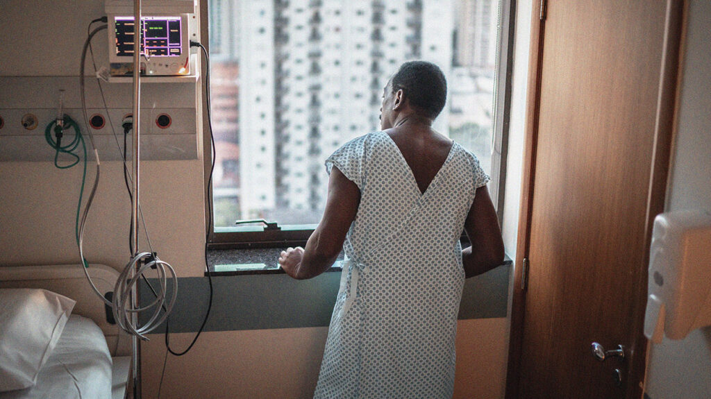An older adult looking out of the window of a hospital room while recovering from blood clots in the lungs.