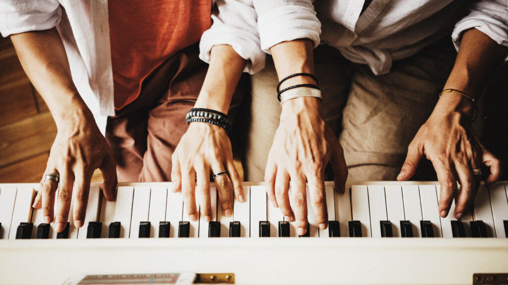Two people playing the piano together as part of music therapy.