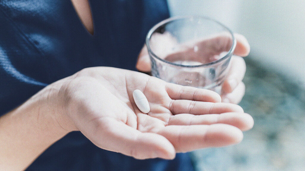 close up of a person's hand holding a pill and a glass of water
