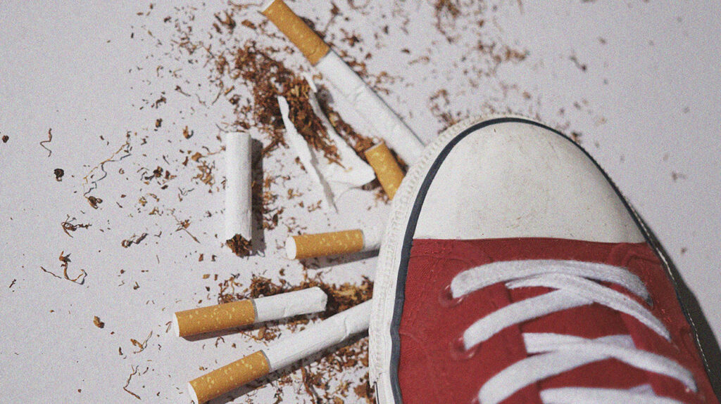 cigarettes are surrounding a person's foot