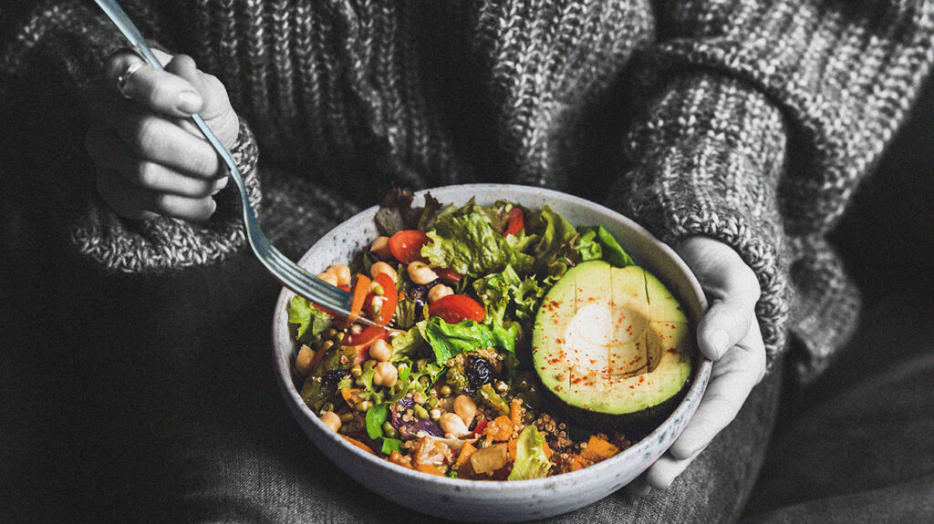 A person eating a bowl of healthy vegetables.