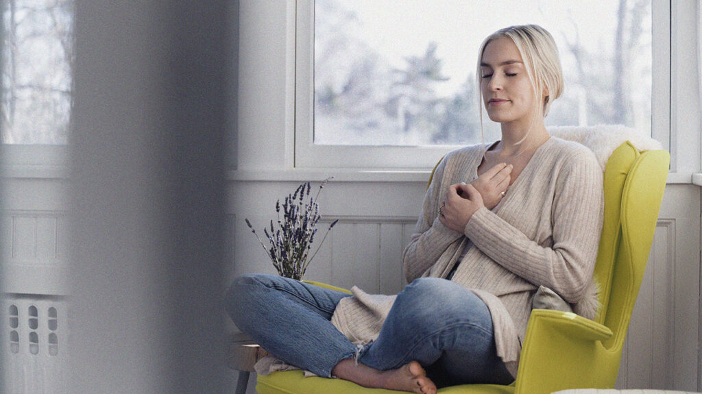 A woman sitting in a yellow armchair with her eyes closed and hands across her chest, practicing a breathing exercise to relax the throat during anxiety.