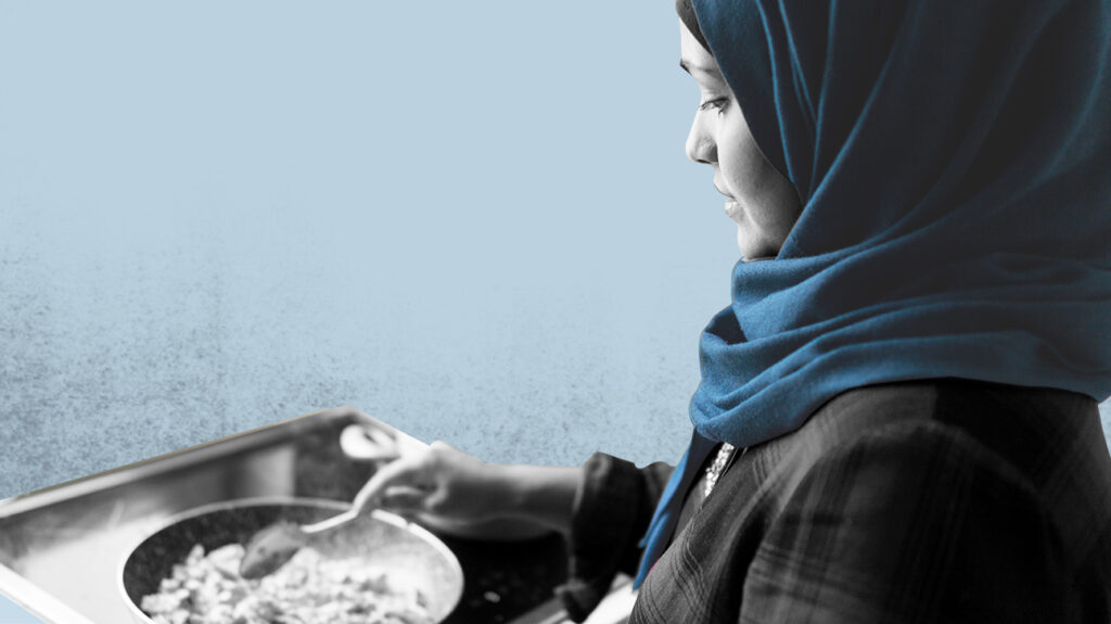 Black and white photo of person wearing a scarf carrying a tray with either a blue apron or green chef meal delivery, isolated over pale blue background