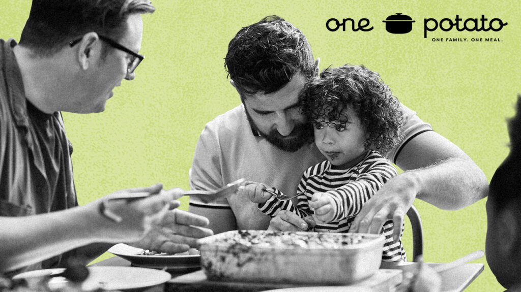 Black and white photo of a family around a table filled with dishes eating one potato meal kit, isolated over green background with brand logo