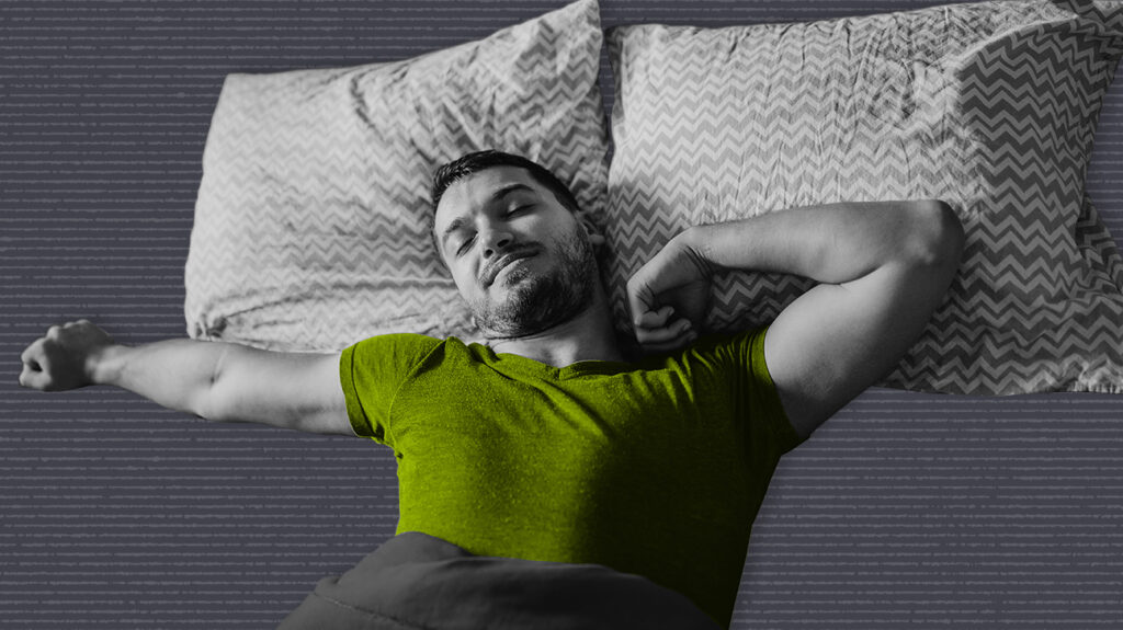 Black and white photo of man asleep on bed and beautyrest black pillows, wearing a green shirt
