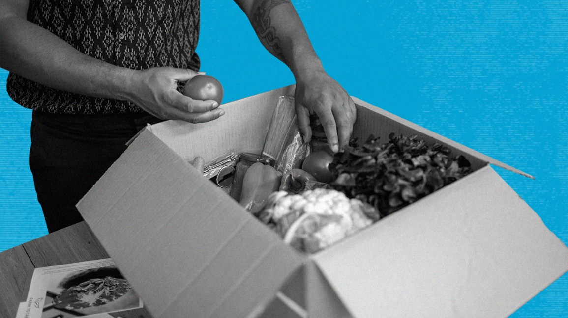 Black and white photo of person taking fruits and vegetables out of meal delivery box from either hello fresh or purple carrot, isolated over blue background
