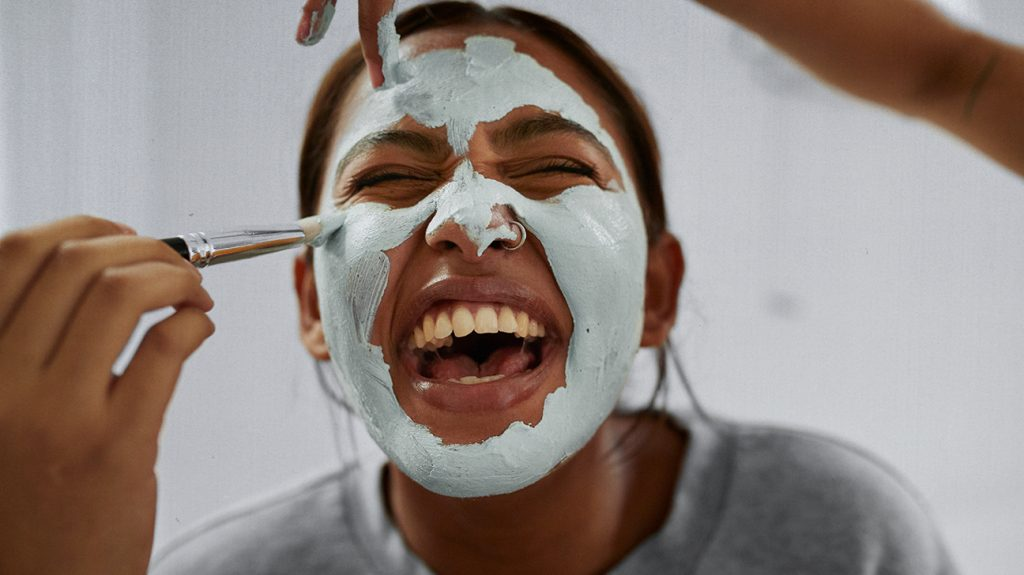 Smiling female receives a facemask as part of a facial.