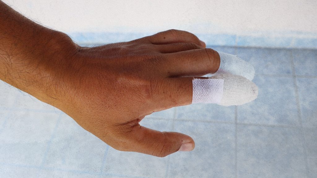 A person's hand with a bandage on their finger.