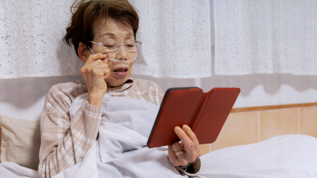 an older adult is looking at their phone in bed. They have a nasal cannula in their nose.