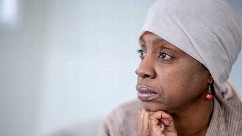 A Black woman with breast cancer looks into the distance