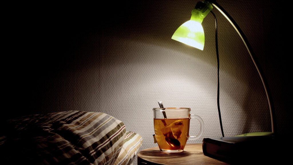 A beverage next to a person's bed, which may help with a hangover.
