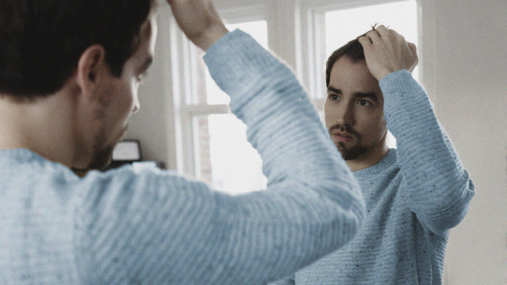 a person looking at their hair in a mirror