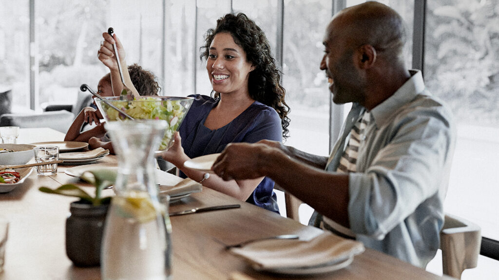 people sitting around at a table laughing and eating