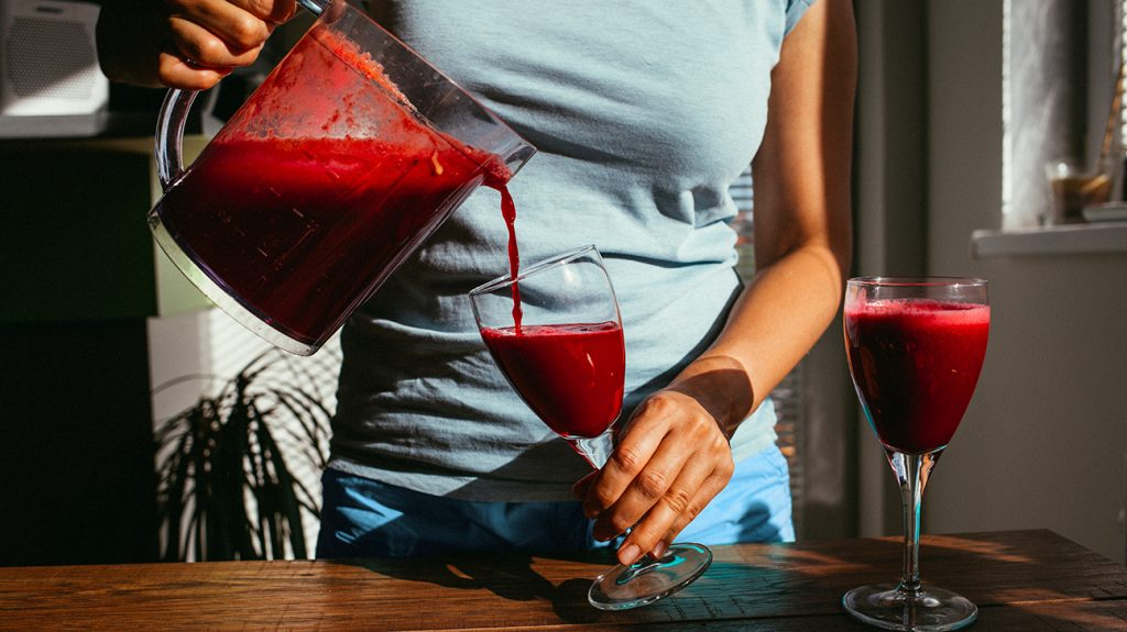 mid shot of woman pouring beetroot juice in a glass