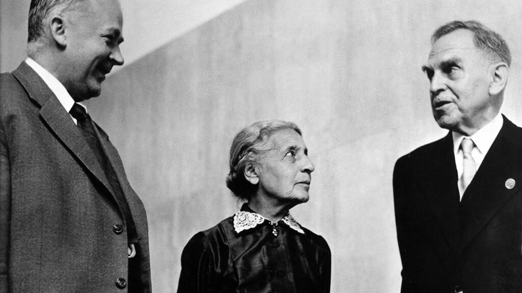black and white photo of Lise Meitner looking up to her male colleagues