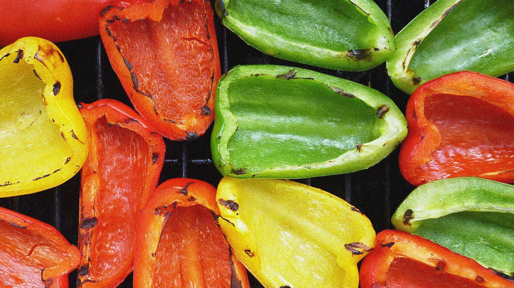 yellow, green, and red bell peppers are halved and being grilled