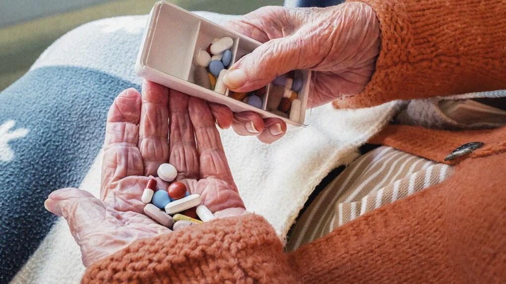 Older adult holding a number of tablets