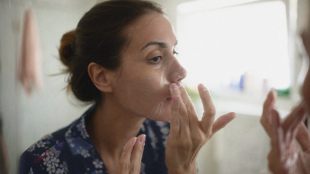 a person applying cream to their face