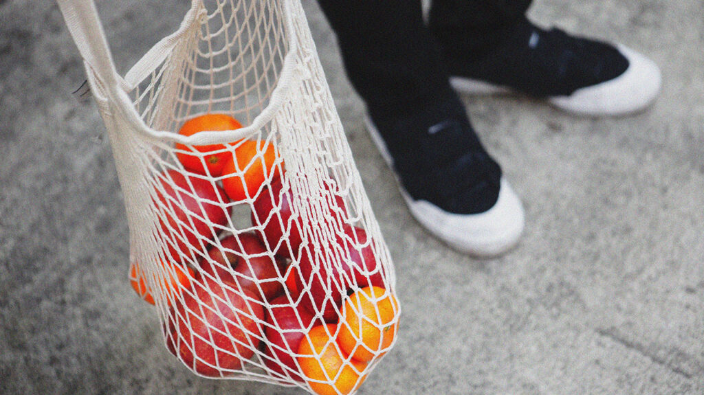 a person is carrying a string grocery bag full of apples and satsumas