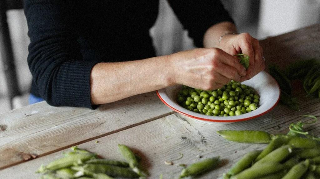 A person shucking peas
