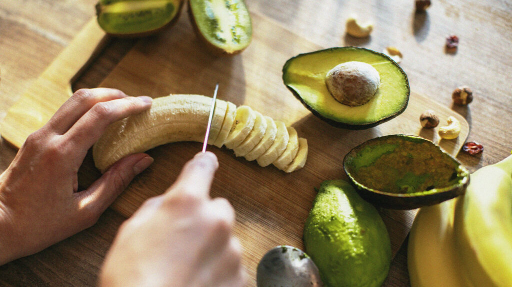 a person is chopping a banana with a knife on a wooden chopping board. There are sliced avocados on the board too.