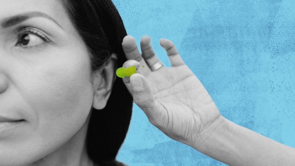 black and white photo of a woman putting a yellow audicus hearing aid into her ear, isolated over blue background