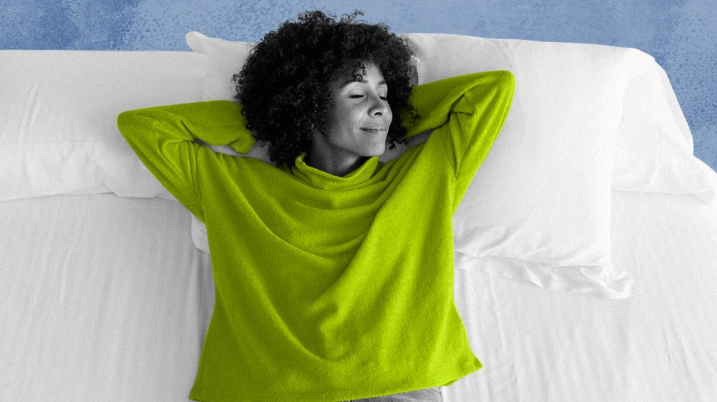 Adult female laying on a bed with her hands behind her head looking to the left, eyes closed and smiling contently, possibly after researching different latex mattress toppers