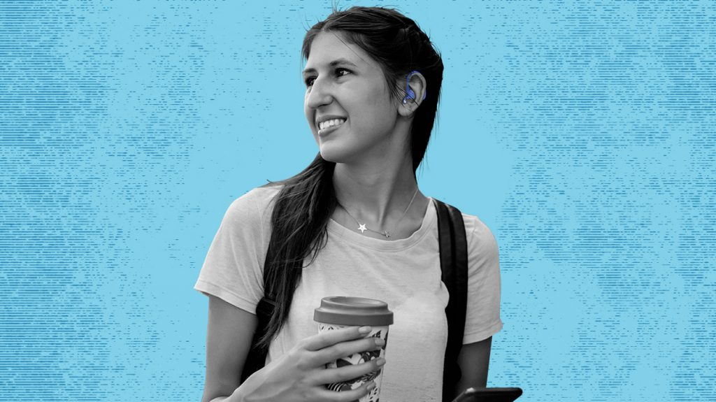Adult female holding a travel mug and wearing a backpack looking to the right with a hearing device in her ear, possibly wearing ReSound hearing aids