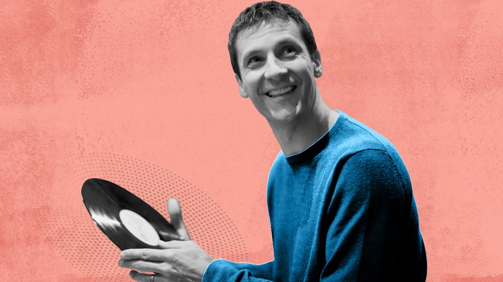 Black and white photo of man holding vinyl record while wearing invisible hearing aid, isolated over pink background