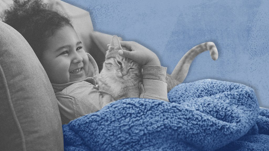 Black and white photo of a child using a blue weighted blanket, isolated over blue background