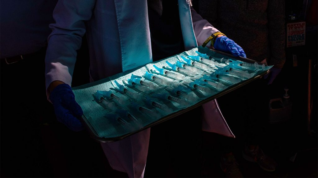 Healthcare professional carrying a tray of mRNA vaccines