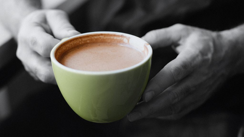 close up of hands holding cup of hot cocoa