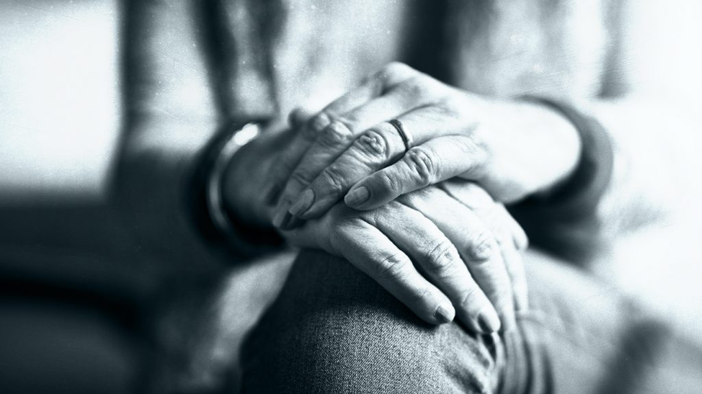 An older person sits with their hands crossed on their lap