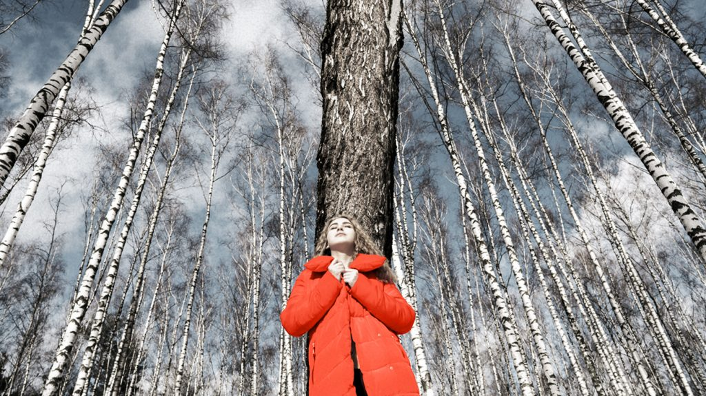 woman wearing red winter coat staring at the sky