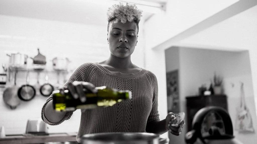 倾吐在她的烹调的妇女橄榄油