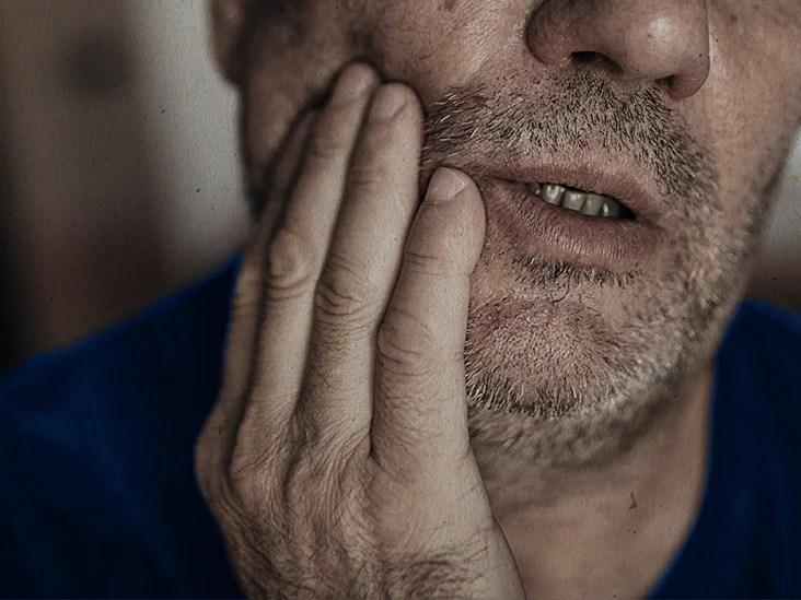 近距离的人,他的牙齿受伤,手捂着下巴