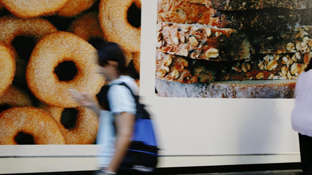 person walking past food poster ads